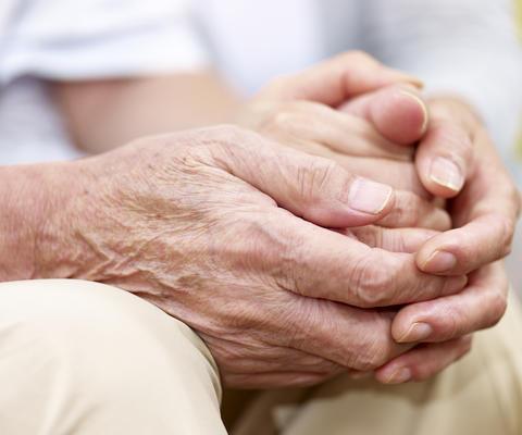 Zwei SeniorInnen halten sich an den Händen.